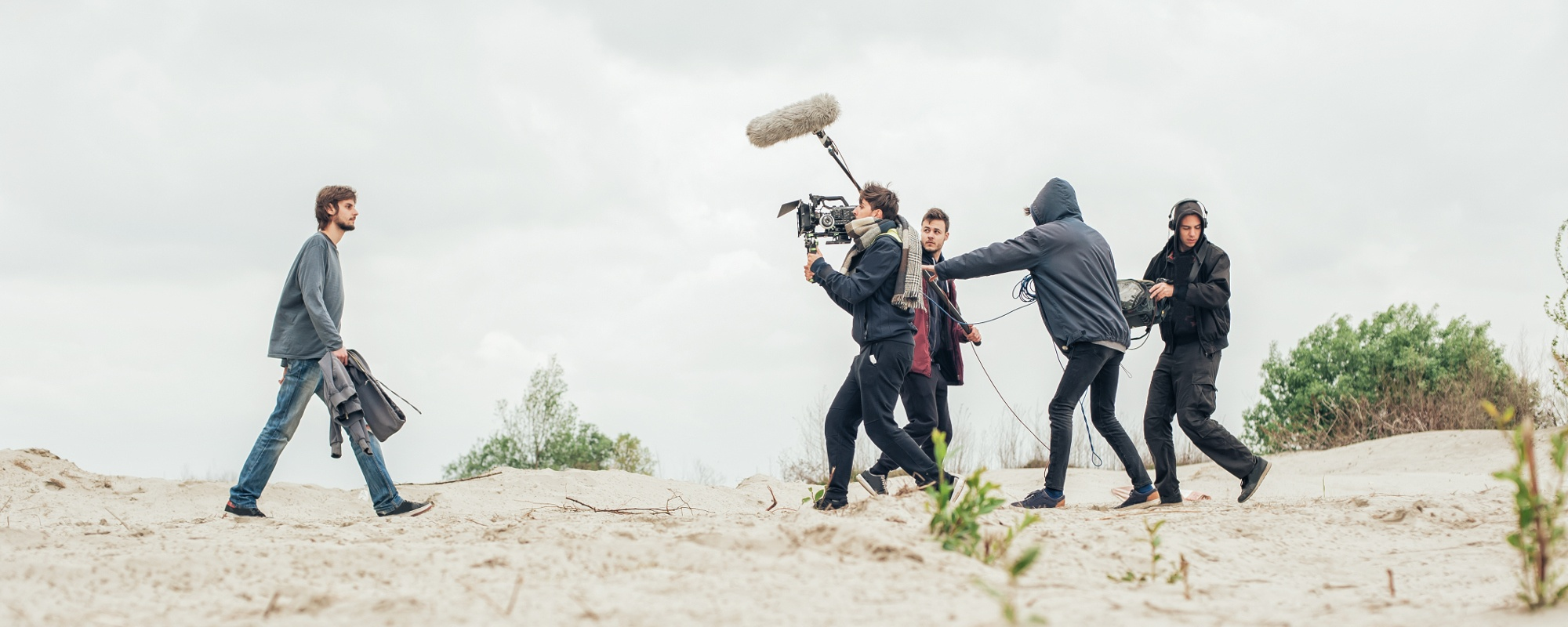 Picture of a film crew recording audio and video for an outdoor scene